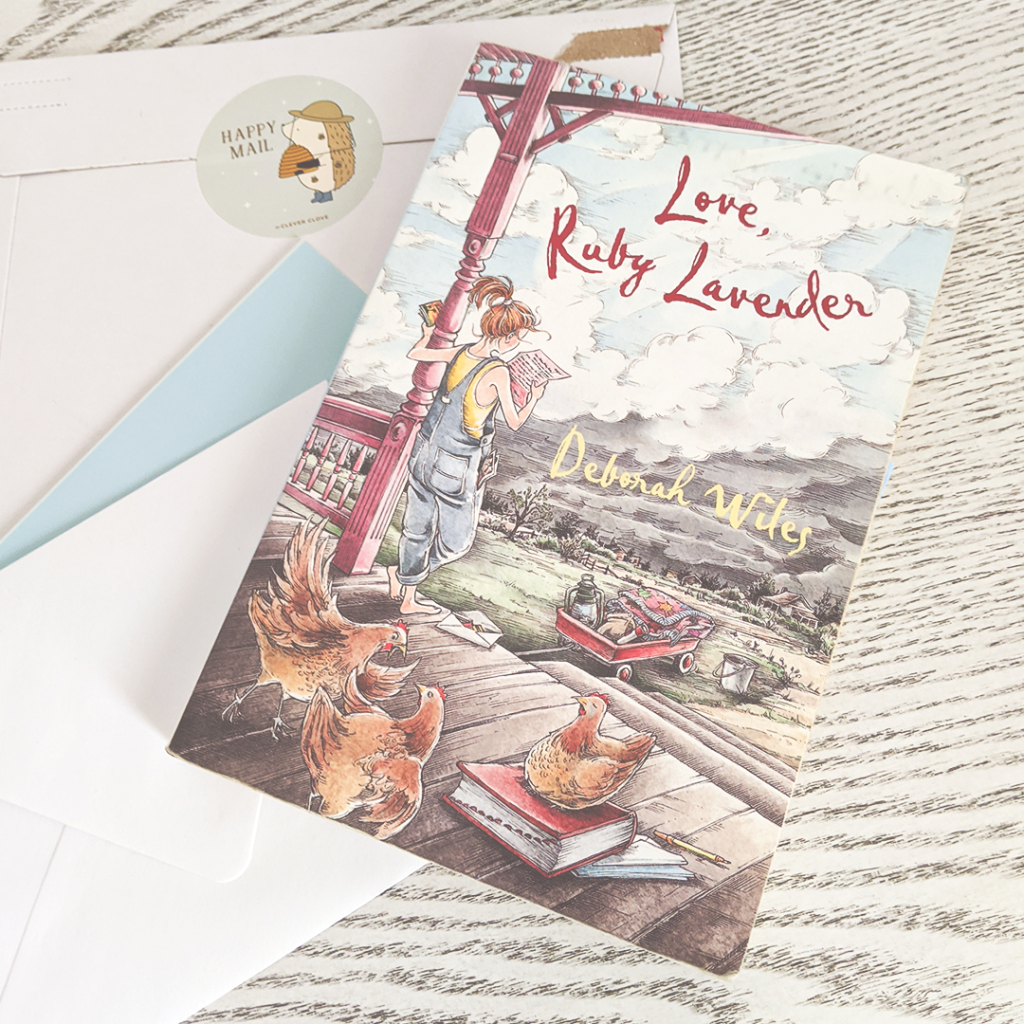 "Bookstagram photo featuring LOVE, RUBY LAVENDER by Deborah Wiles. The book rests atop a pile of letters and a package sealed with a sticker. The sticker reads ""Happy Mail"" and depicts a small cartoon hedgehog wearing a beekeeper's hat and holding a bee hive in gloved hands."