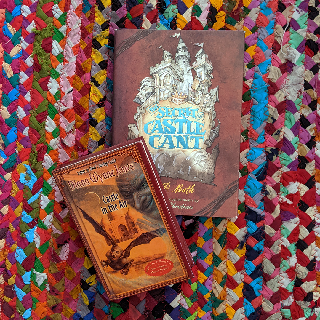 Photograph featuring the books CASTLE IN THE AIR by Diana Wynne Jones and THE SECRET OF CASTLE CANT by K. P. BELL. The books are lying on a colorful braided rug.