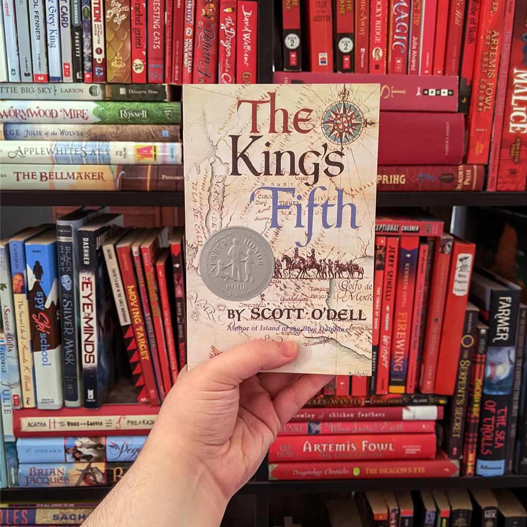 Photograph features the book THE KING'S FIFTH by Scott O'Dell. Elza holds the book up against a bookshelf organized in rainbow order.