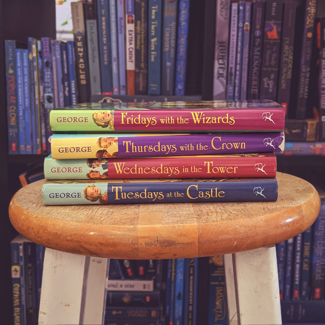 Photograph features four titles from THE CASTLE GLOWER series by Jessica Day George stacked on a stool in front of a bookshelf arranged in rainbow order.
