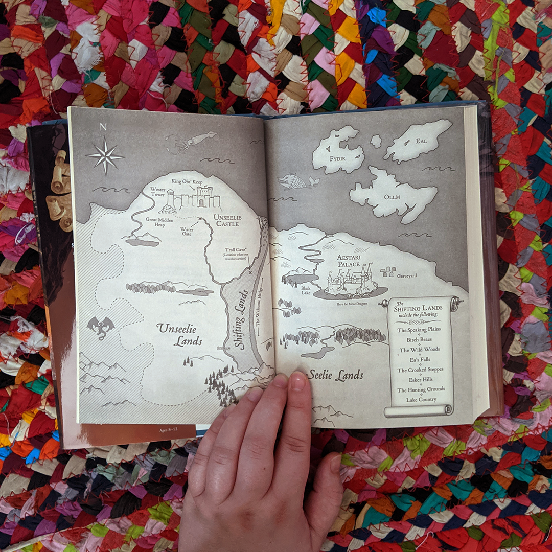 Photograph features the book THE HOSTAGE PRINCE by Jane Yolen & Adam Stemple which is opened to the illustrated map of the fictional world of The Shifting Lands. Elza's hand rests at the bottom of the book which is lying open on top of a colorful braided rug.