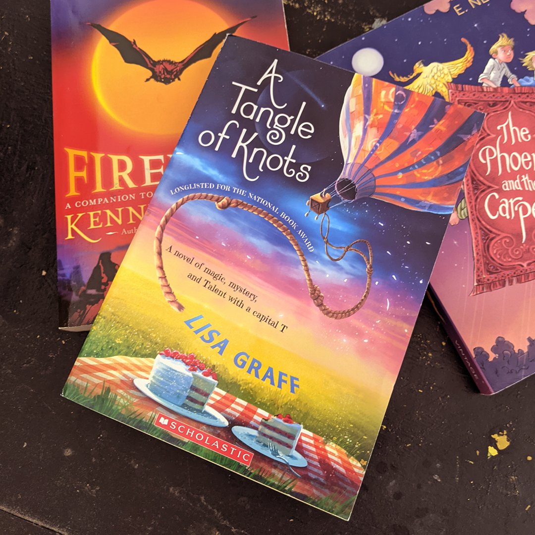 Bookstagram photo features the books FIREWING by Kenneth Oppel; THE PHOENIX AND THE CARPET by E. Nesbit; and A TANGLE OF KNOTS by Lisa Graff.