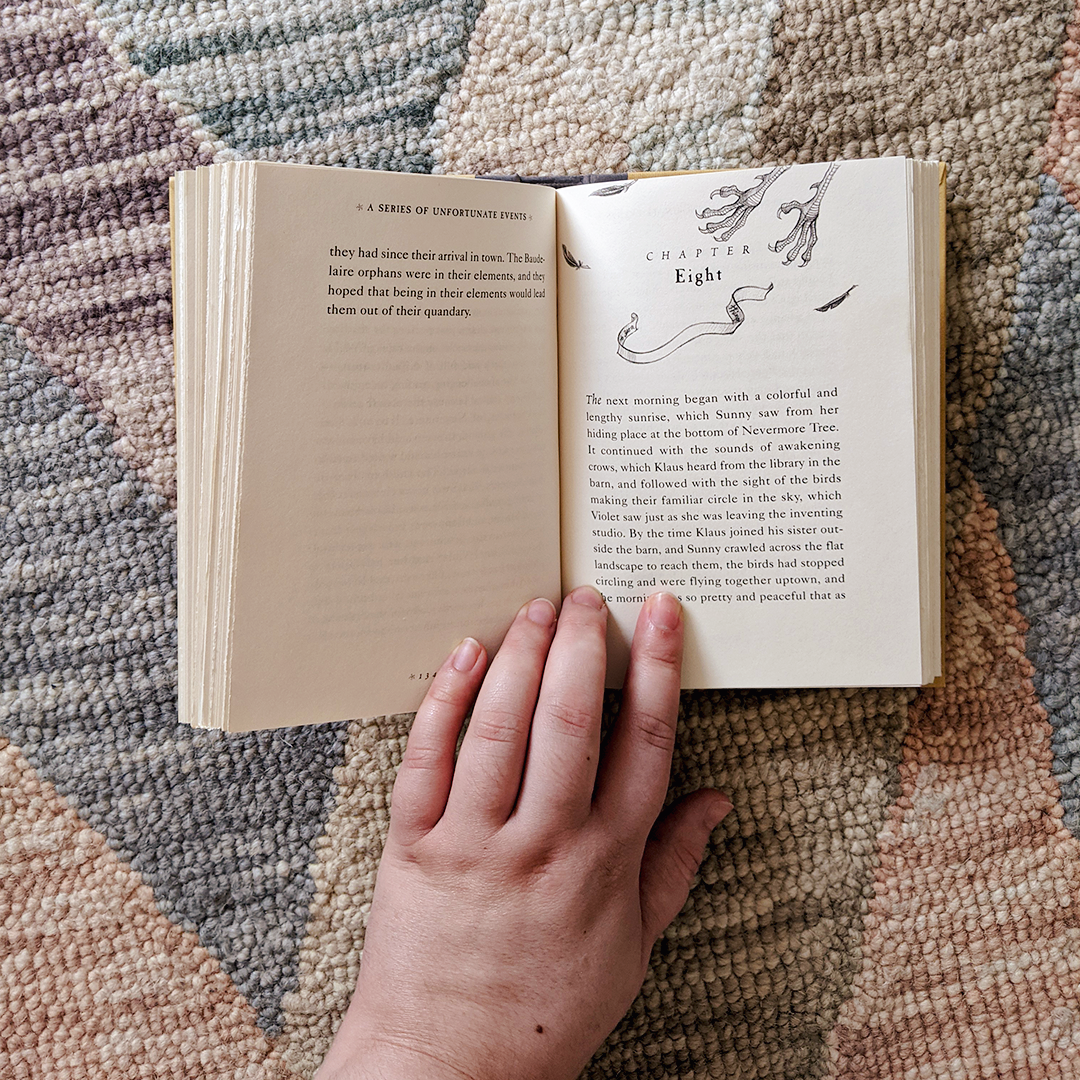 Bookstagram photo features the book THE VILE VILLAGE by Lemony Snicket laying open on a rug. Elza's hand holds it open to Chapter Eight, which features the talons of a crow and a few scattered feathers above the chapter heading.