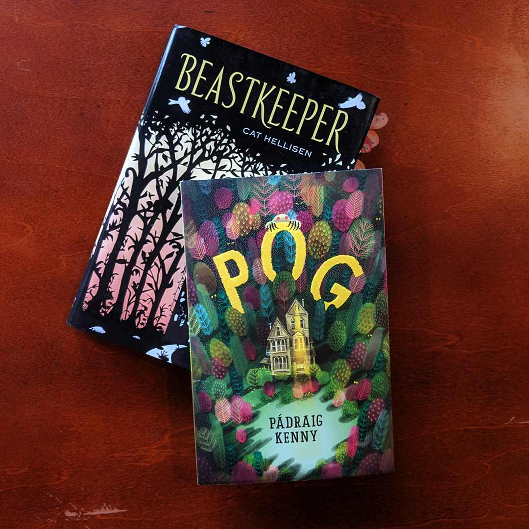 Bookstagram photo features the books BEASTKEEPER by Cat Hellisen and POG by Padraig Kenny laying on a wooden surface.